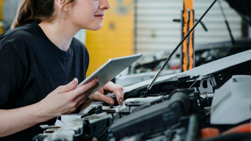 Female mechanic running a diagnostic on a car engine