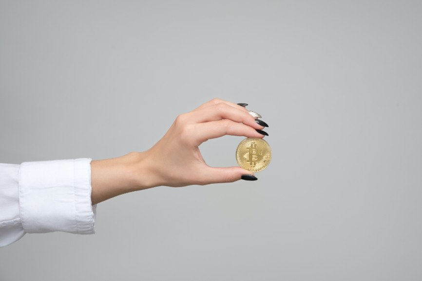 extended arm of woman holding Bitcoin