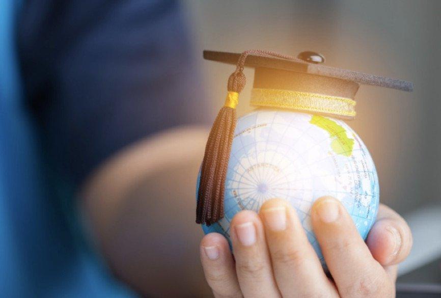 Hand holding globe. with graduation cap