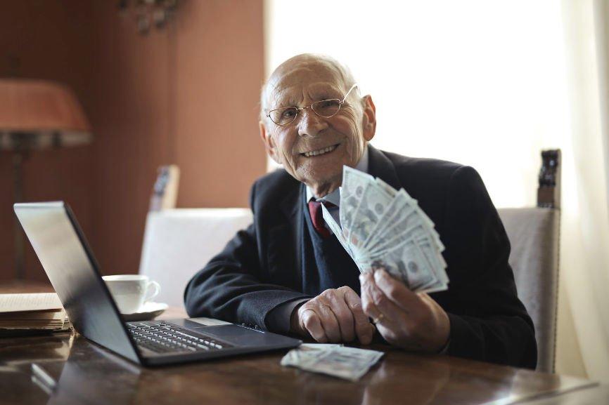 Older man behind a desk holding money
