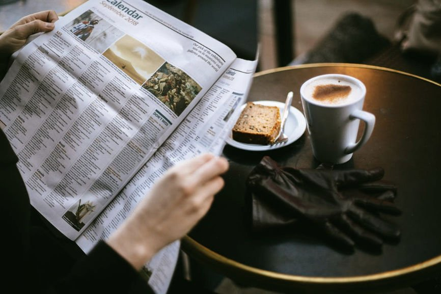 Person Reading Newspaper in Cafe