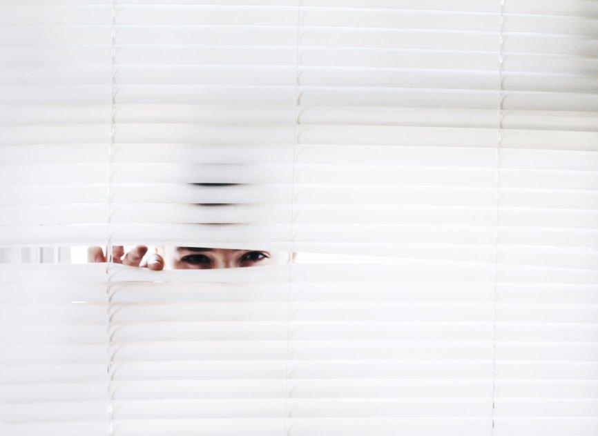 Person peering through blinds
