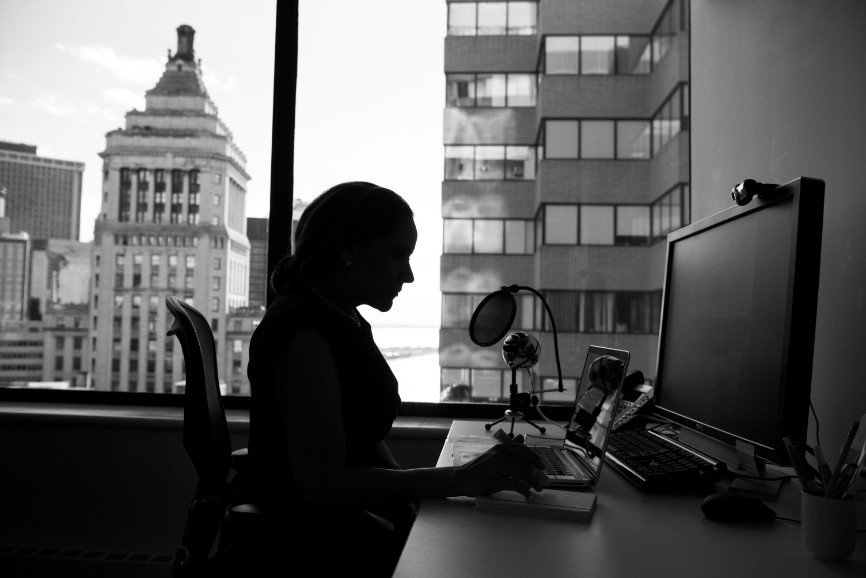 Woman sitting at computer in front of widow with city view.