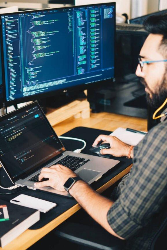 Man Sitting at laptop Coding