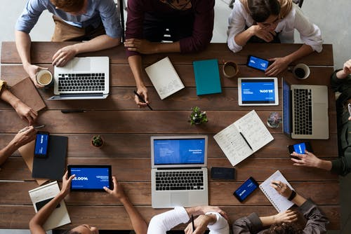 People with laptops seated at conference table