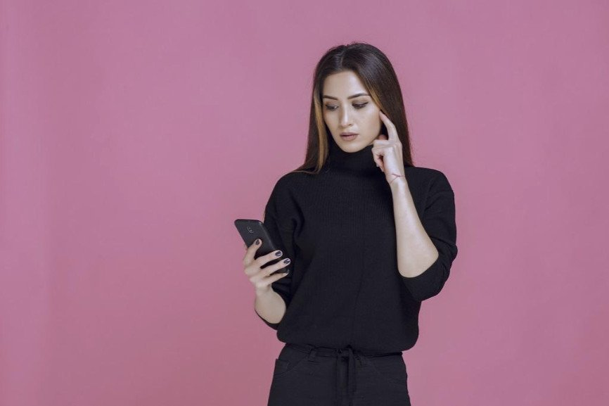 Woman Dressed in Black looking at a cell phone