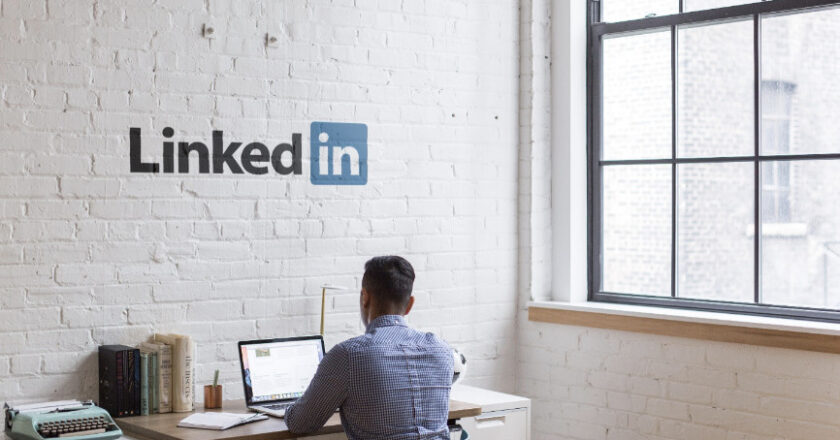 Man sitting at laptop with LinkedIn sign on the wall