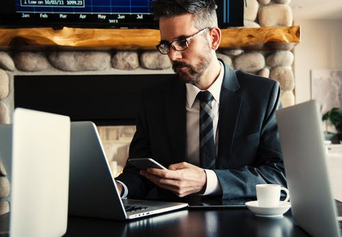 Man seat at computer holding smartphone