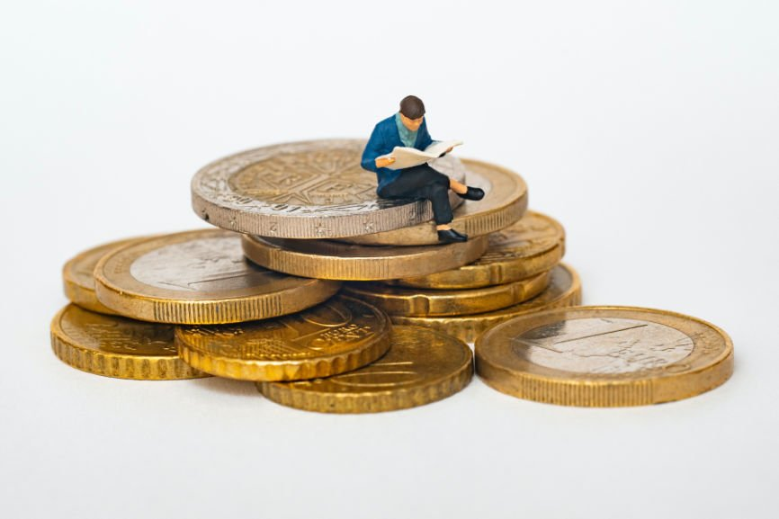 Illustration of a man reading paper siting on a stack of coins
