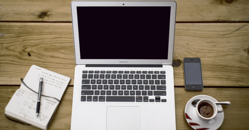 Notepad, MacBook, iPhone and coffee on wooden table
