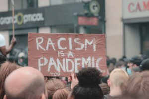 """Crowd holding sign that reads, """"Racism is a Pandemic"""""""