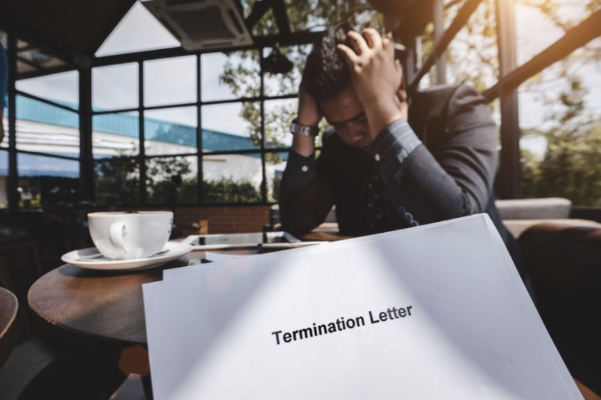 Man with head in hands over termination letter