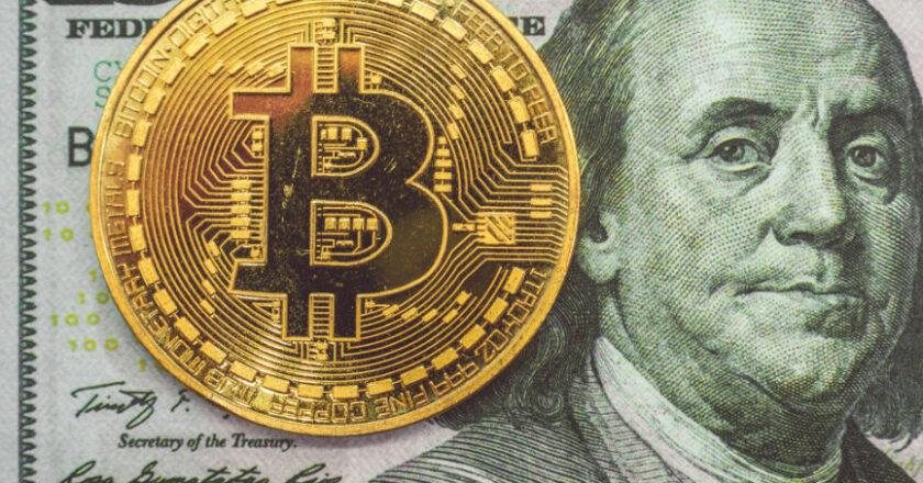 $100 dollar bill below a single bitcoin