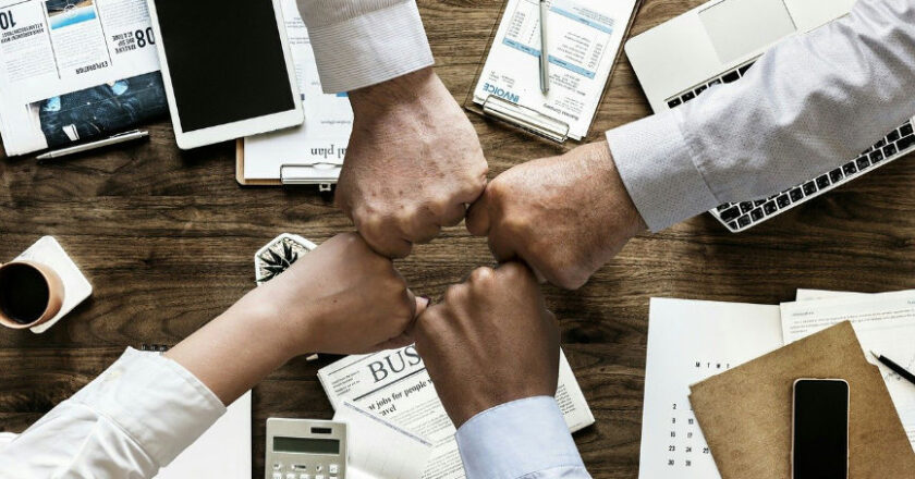 Four people fist bumping over a desk