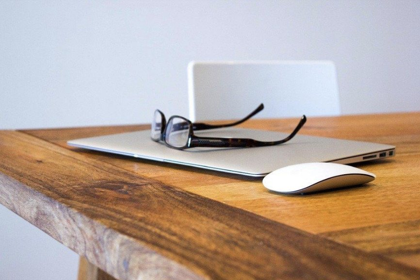 MacBook, Mouse, and glasses on wooden table
