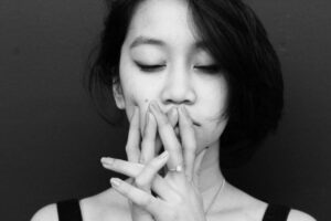 Woman with eyes closed and hands to mouth