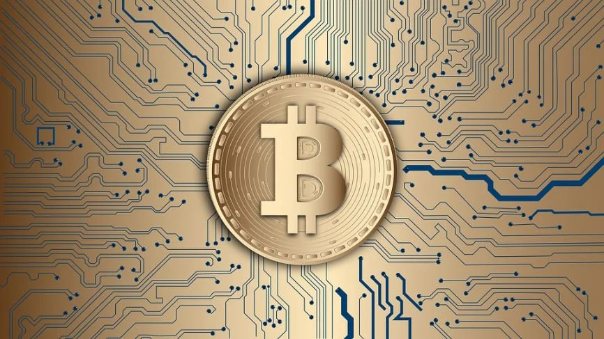 Abstract drawing of a bitcoin on top to a gold circuit board