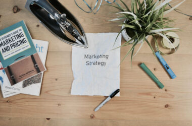 """Wooden taple with a marketing book and paper that reads """"Marketing Strategy"""""""