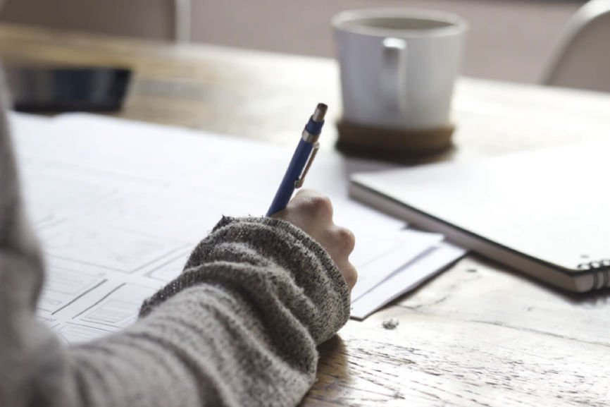Person writing while seated at a desk with a cup of coffee