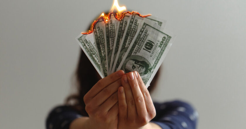 Woman holding $100 bills that are burning