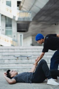 Man being helped up after falling
