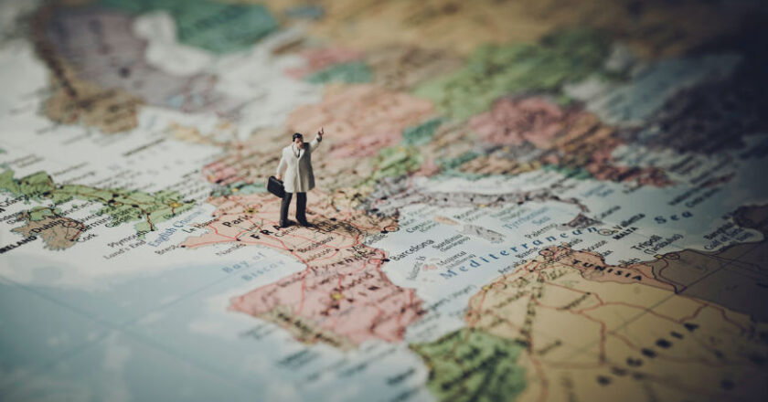 Figure standing on a world map, global outsourcing