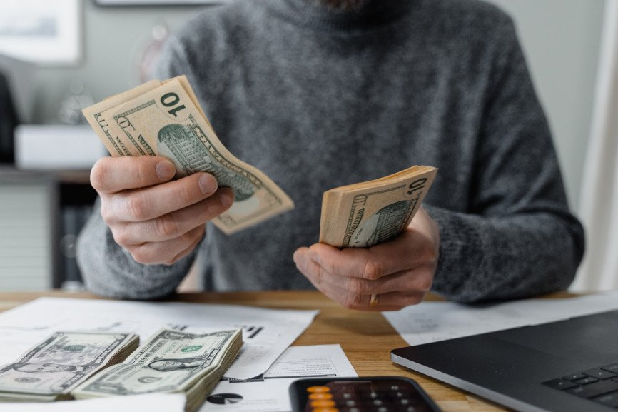 Man seated at desk counting money preparing payroll