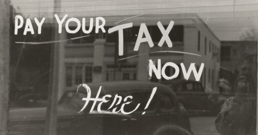 """Sign drawn on glass window that reads """"Pay Your Tax Now, Here!"""""""