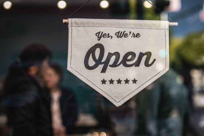 """Sign on store window that reads, """"Yes we're open"""""""