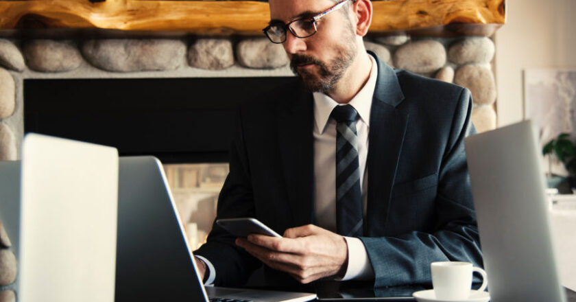 Man iin Suit looking at laptop and smartphone