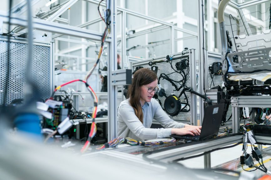 Woman working at computer in a manufacturing setting