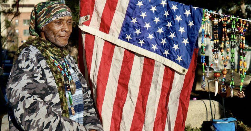 Military veteran standing next to American flag