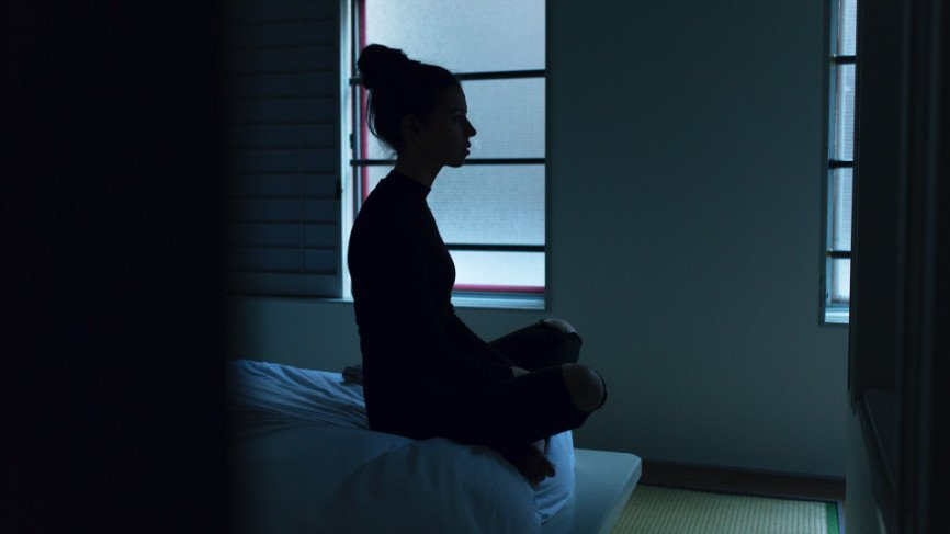 Woman with insomnia sitting up in bed.