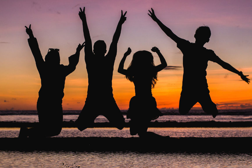 Silhouette of people jumping while facing a sunset