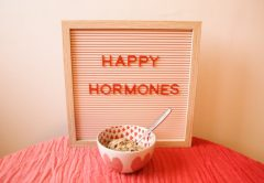 """Sign displaying the words """"Happy Hormones"""" behind a bowl of cereal"""