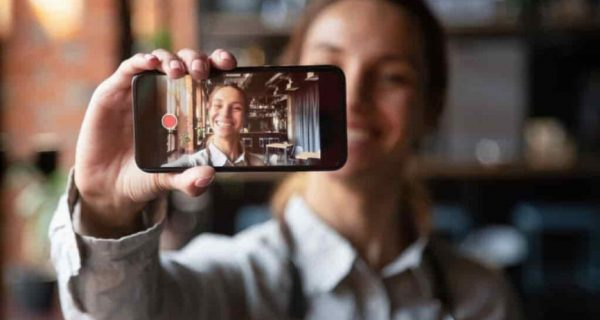 Woman holding iPhone with video playing