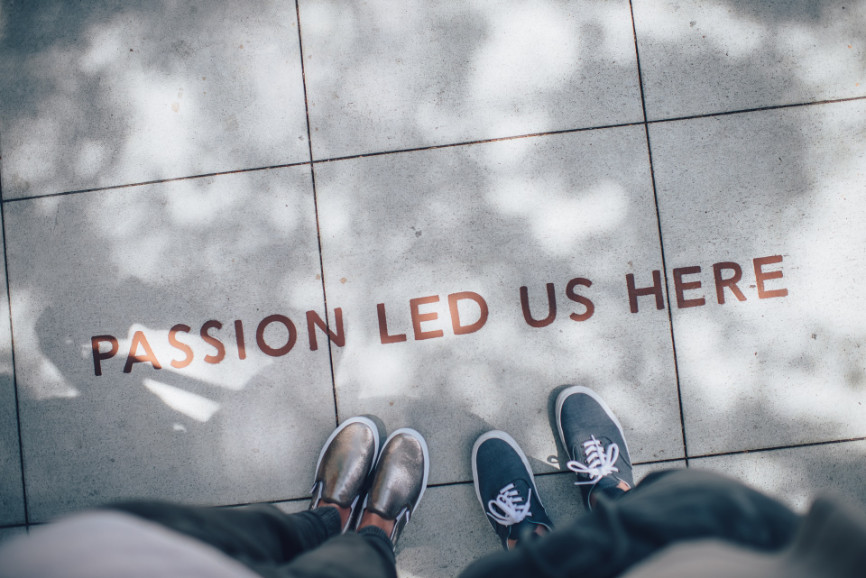 """People standing on tiles that read, """"Passion Lead Us Here"""""""