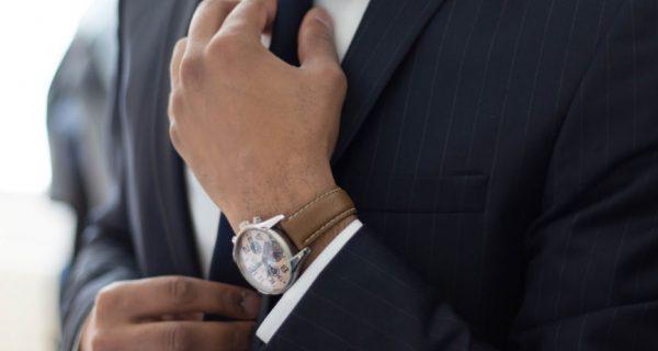 Man in a suit straitening his tie