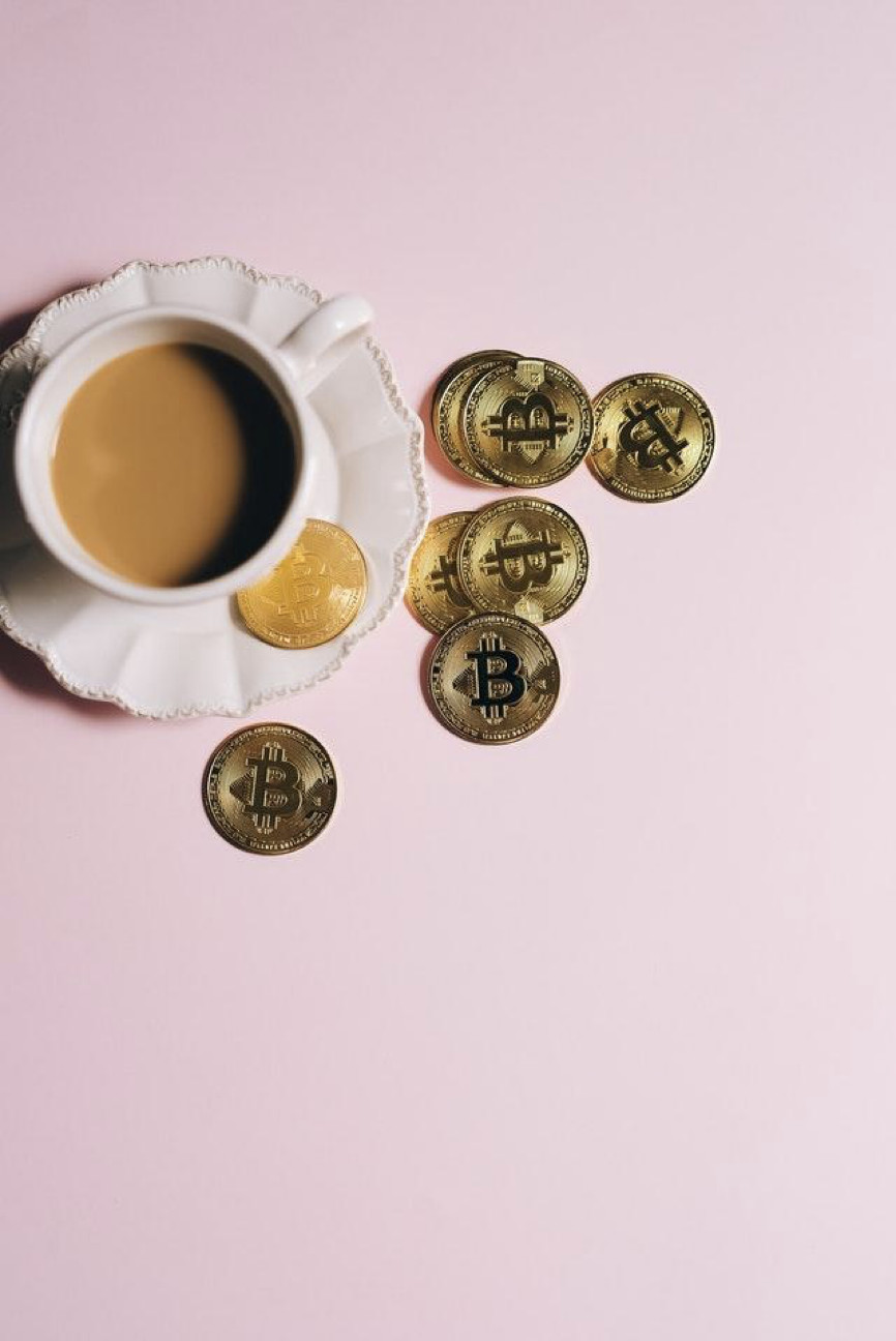 Cup of Coffee and Bitcoins on a Pink background
