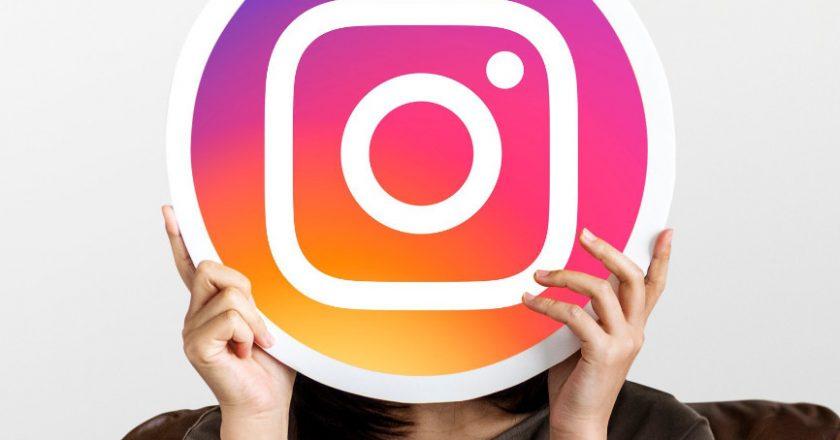 Girl holding Instagram Logo in front of her face