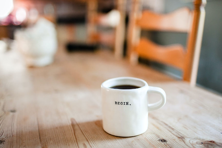 """Cup of coffee with the word """"Begin"""" representing starting a business"""