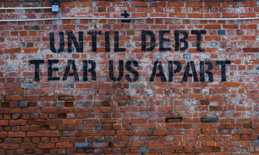 "Brick Wall displaying the words ""Until Debt Tear Us Apart"""