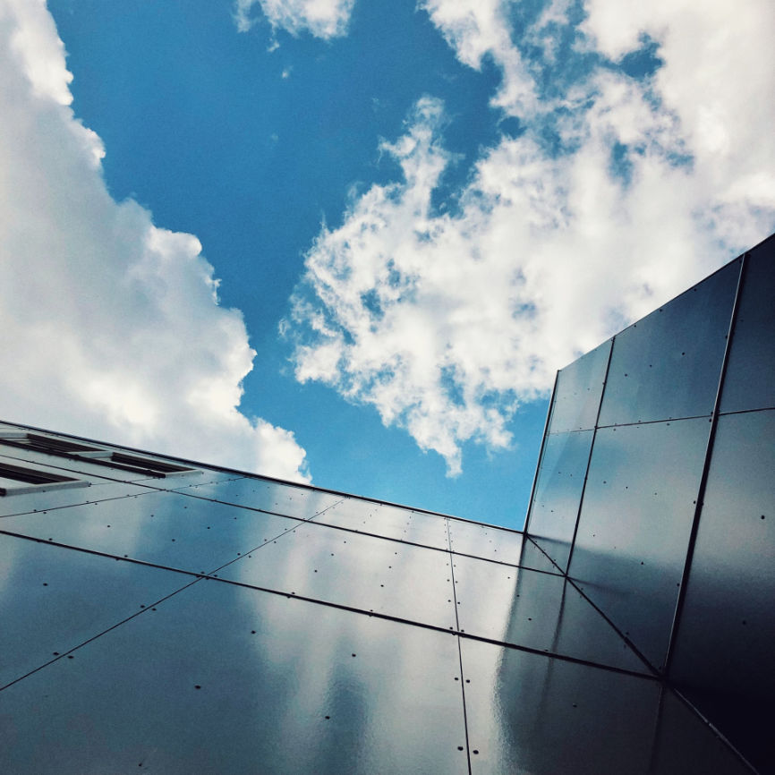 Bluesky and clouds behind modern building representing Microsoft Azure AZ-204 Certification