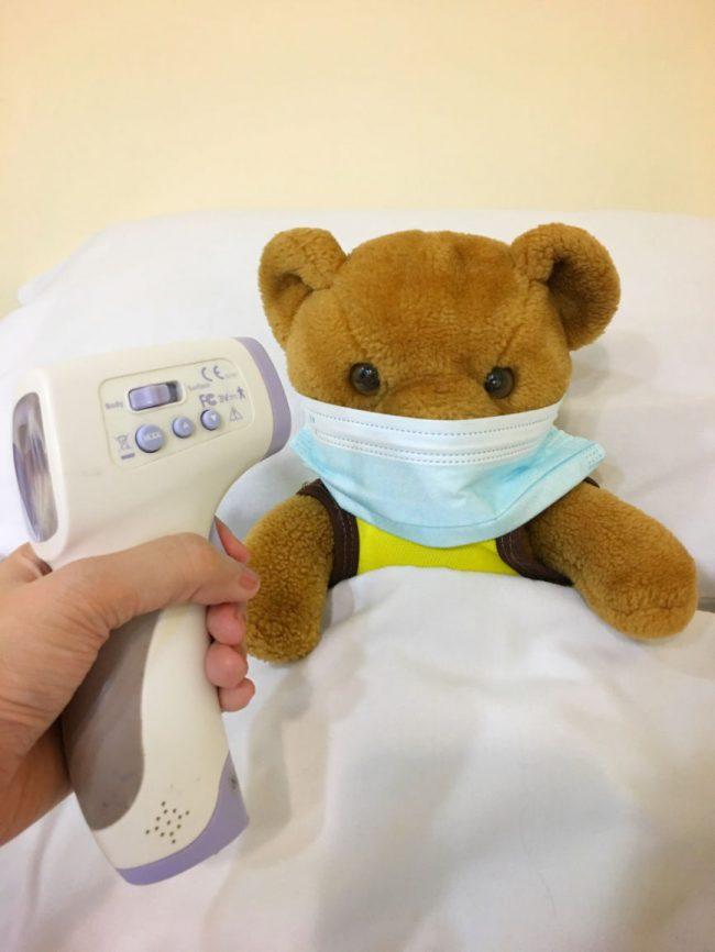 Teddy bear in bed having its temperature taken