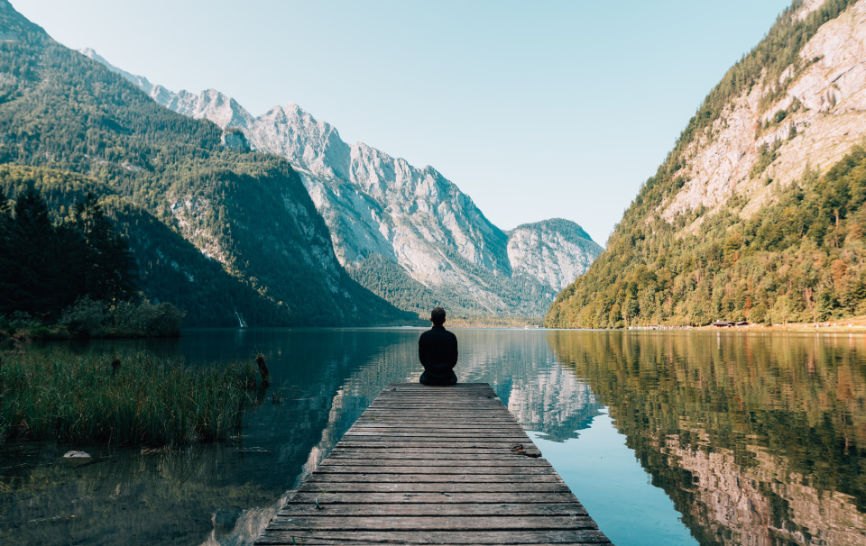Person sitting at the end of a pier meditating