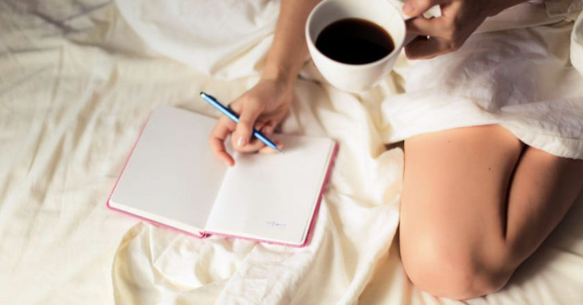 Woman in bed with coffee and journal