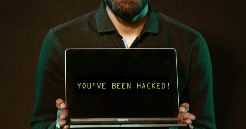 """Man holding laptop displaying the words, """"You've been hacked"""""""