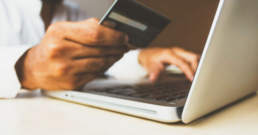 Man holding credit card in front of laptop