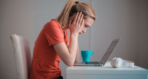 Worried Student Staring At Laptop. Parent PLUS Loans