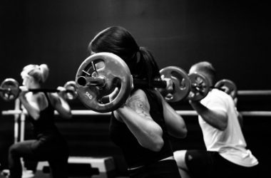 Group of people exercising with barbell